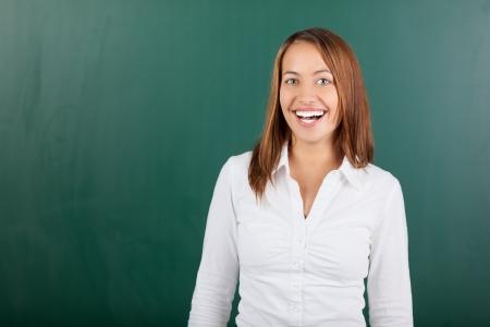 Portrait of cheerful female teacher standing against chalkboard Stock Photo - 21167639