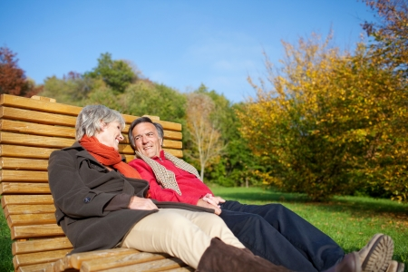 unwinding: Senior couple relaxing in the autumn sun reclining side by side on a comfortable curved wooden bench in a park or garden