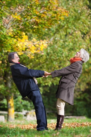 male senior adult: Happy romantic couple holding hands and pulling each other