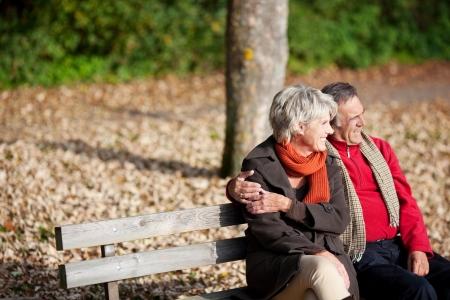 何かを見ながらベンチ公園に座っている笑顔の年配のカップル
