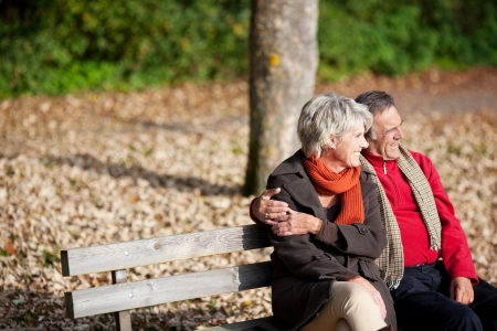 Smiling senior couple sitting on the bench park while looking at something 版權商用圖片