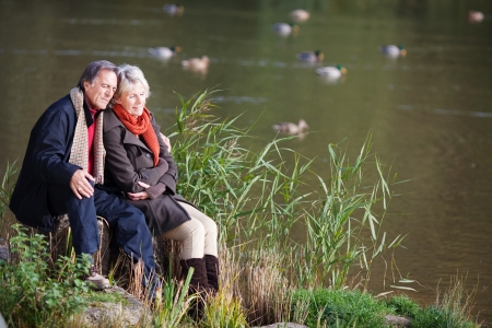 Loving mature couple sitting and looking on the river side photo
