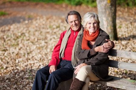 banc de parc: Beau couple de personnes âgées assis sur le banc dans le parc