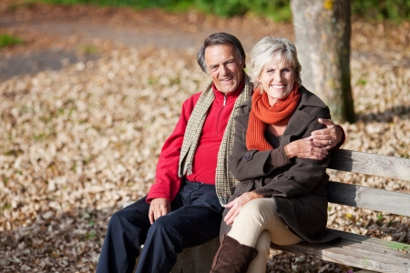 Lovely senior couple sitting on the bench in the park