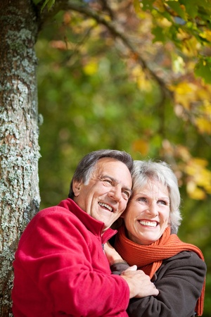 couple laughing: Happy old couple laughing while looking at something in the park Stock Photo