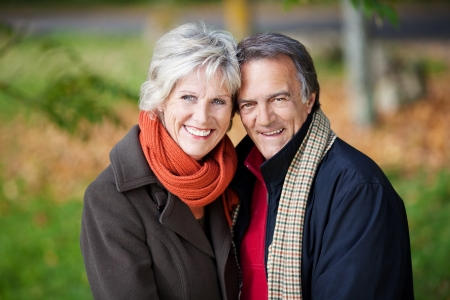 scarves: Happy mature couple posing over the outdoors background Stock Photo