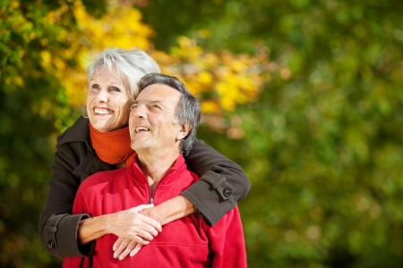 older couples: Senior couple smiling and looking at something in the park