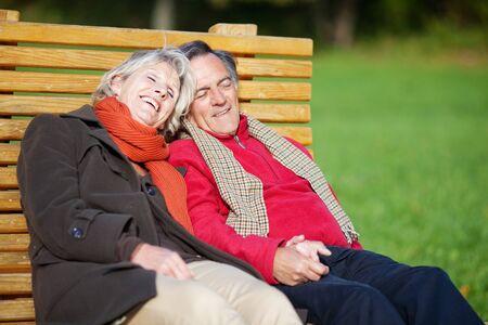 Senior couple enjoying the sun on a bench in a park photo