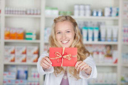 Female pharmacist holding bonus coupon card gift in pharmacy Stock Photo - 21170276