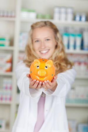 Portrait of female pharmacist holding piggy bank in pharmacy photo