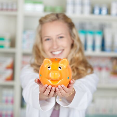 Portrait of young female pharmacist holding piggybank in pharmacy photo