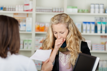 coughing: Female customer coughing in front of pharmacist holding prescription paper in pharmacy