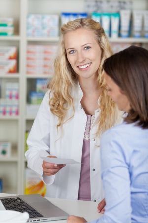 Young female pharmacist looking at camera at pharmacy photo