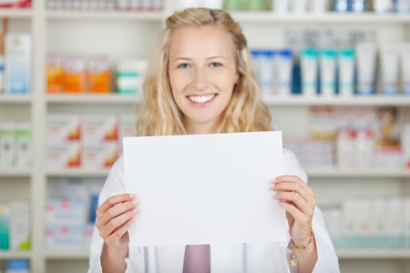 Young blond female pharmacist holding blank paper in pharmacy