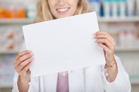 midsection: Young female pharmacist holding blank paper in pharmacy Stock Photo