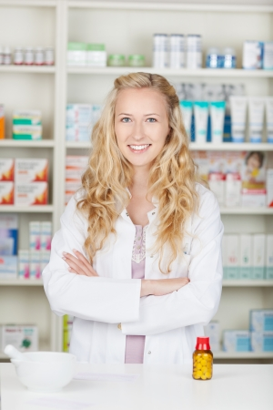 serious pharmacist chemist woman standing in pharmacy drugstore photo