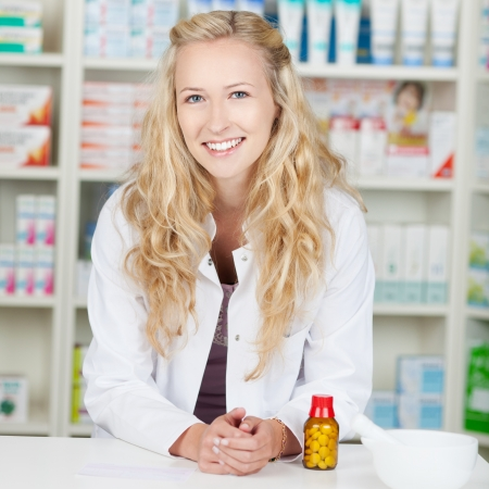 Young blond smiling female pharmacist in pharmacy photo
