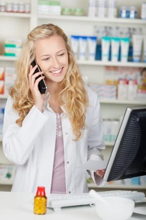 Portrait of happy female pharmacist communicating on phone in pharmacy Stock Photo - 21174239