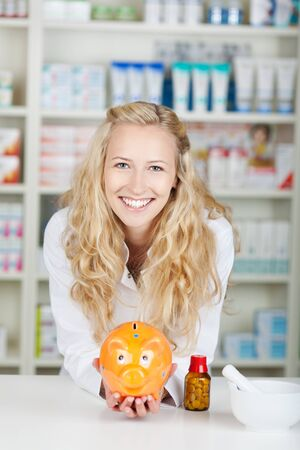 waistup: Portrait of young female pharmacist with piggy bank in pharmacy