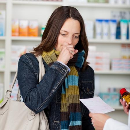 tosiendo: Mediados de adultos tos clienta mientras miraba las manos que sostienen el papel del farmacéutico prescripción y botella de la medicina en la farmacia
