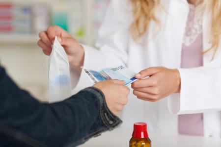farmacia: Sezione centrale di farmacista femmina ricevere denaro dal cliente per il medicinale alla farmacia