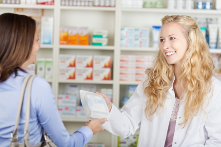 Young female pharmacist giving paperbag of medicine to customer in pharmacy