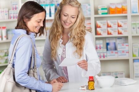 若い薬剤師と処方薬局カウンターにて紙を読む女性客 写真素材