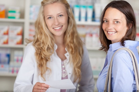 Happy female smiling customer with a pharmacist in a pharmacy photo