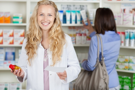 Young pharmacist with prescription paper and female customer in pharmacy photo