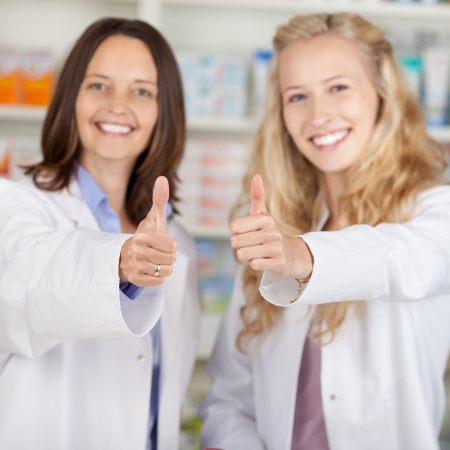 thumbsup: Portrait of confident female pharmacists gesturing thumbsup in pharmacy