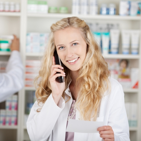 Portrait of young female pharmacist holding prescription paper while using cordless phone in pharmacy Stock Photo - 21170329