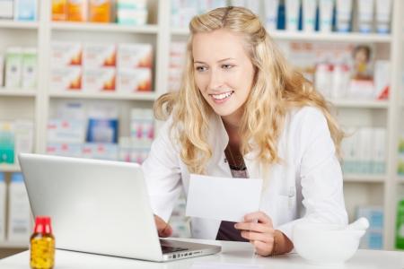 drugstore: Retrato de mujer joven sosteniendo prescripción farmacéutico, mientras que usando la computadora portátil en el mostrador de la farmacia Foto de archivo