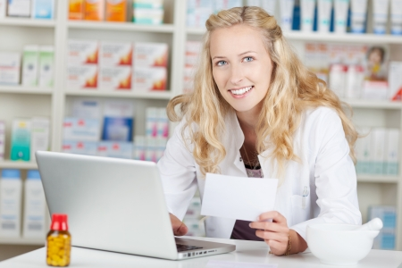 Portrait of young female pharmacist holding prescription paper while using laptop at pharmacy counter Stock Photo - 21170364