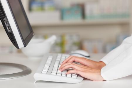 약국 카운터에서 컴퓨터 키보드에 입력하는 약사의 손 확대 사진 스톡 콘텐츠