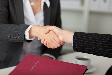 applicant: Young businesswoman shaking hands with candidate during an interview at desk Stock Photo
