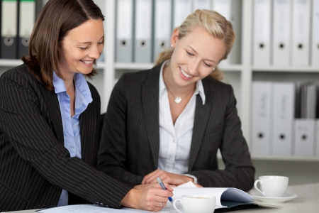 Happy businesswomen working on file at office desk