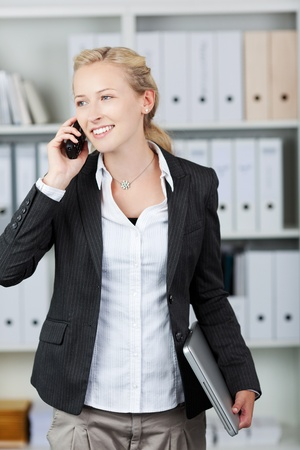 cordless: Happy young businesswoman holding laptop while using mobile phone in office Stock Photo