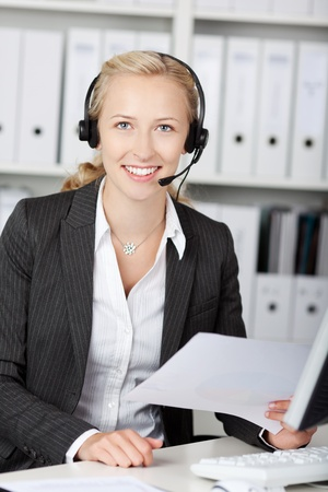 Portrait of young customer service representative using headphones while holding paper at desk photo