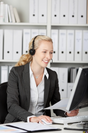 Closeup of female blond customer service executive using headset in office