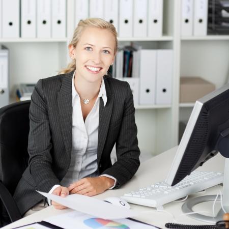Portrait of confident businesswoman holding paper at office desk Stock Photo - 21170406