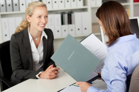 cv: Mediados de adultos de negocios la lectura de CV del candidato mujer en el mostrador de la oficina