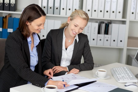 Portrait of young confident businesswomen sitting at office desk photo
