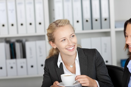 Happy young businesswoman having coffee with coworker in office Stock Photo - 21174286