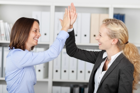 five people: Side view of happy businesswomen fiving high five in office