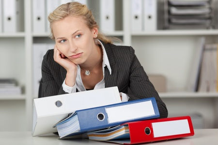 Bored blond businesswoman with stack of binders in office photo