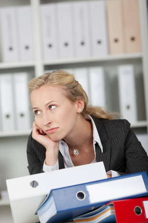 overloaded: Bored businesswoman with stack of binders in office Stock Photo