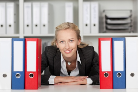 Thoughtful young businesswoman behind binders sitting at office desk photo
