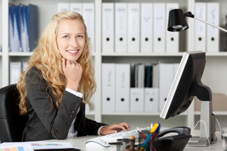 Happy young smiling businesswoman using computer at desk in office photo