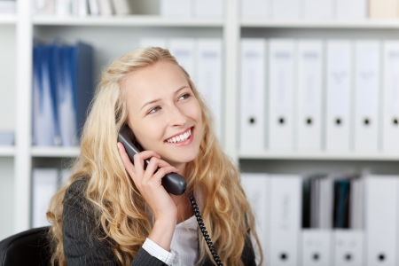 answering call: Happy blond woman in office talking on phone in her office