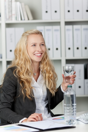 Portrait of happy young businesswoman with water in glass at office